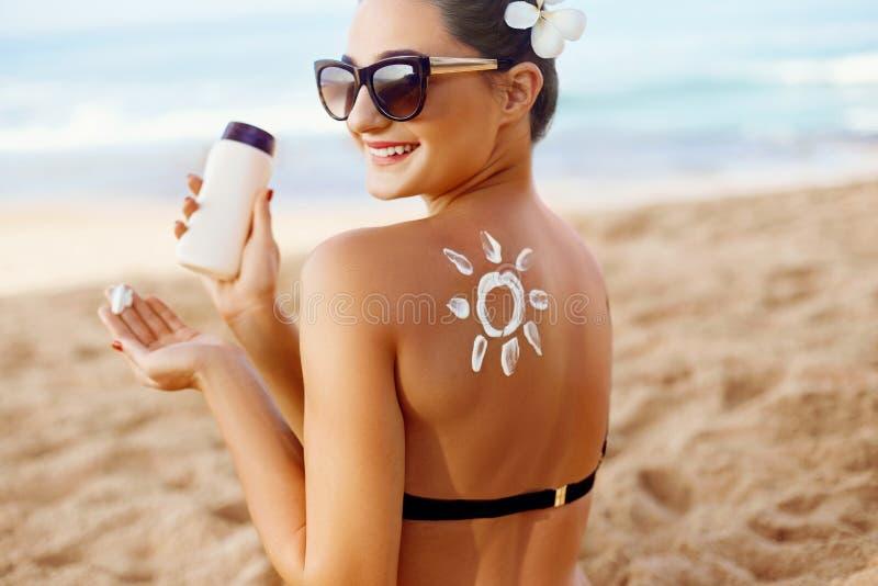 La donna applicarsi espone al sole la crema sulla parte posteriore abbronzata Cura del corpo e della pelle Protezione di Sun Ritr fotografie stock libere da diritti