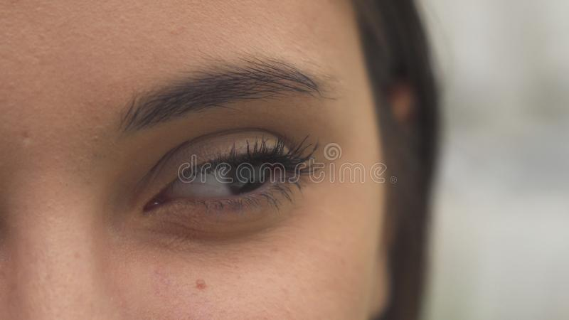 La donna apre il suo occhio fotografia stock