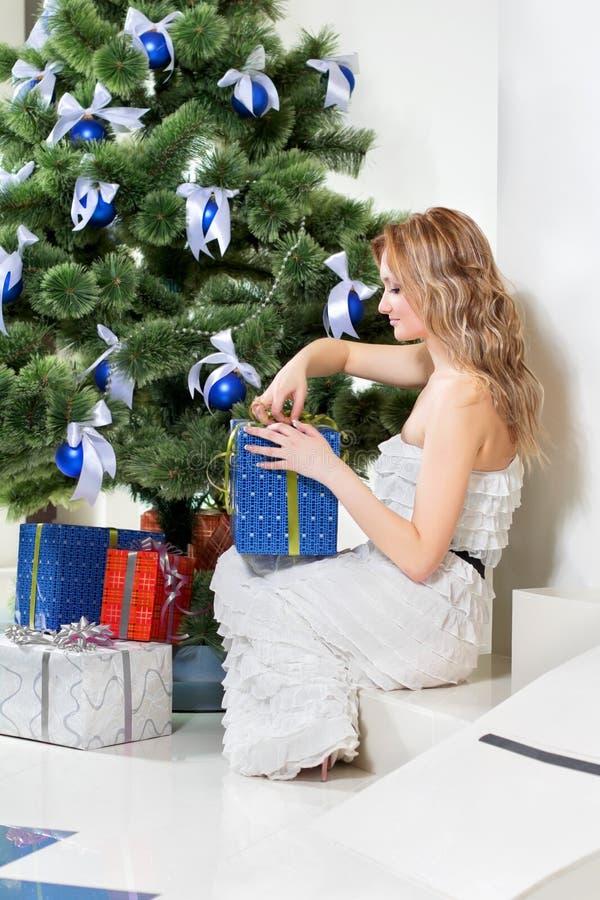 La donna apre un regalo di Natale fotografie stock libere da diritti