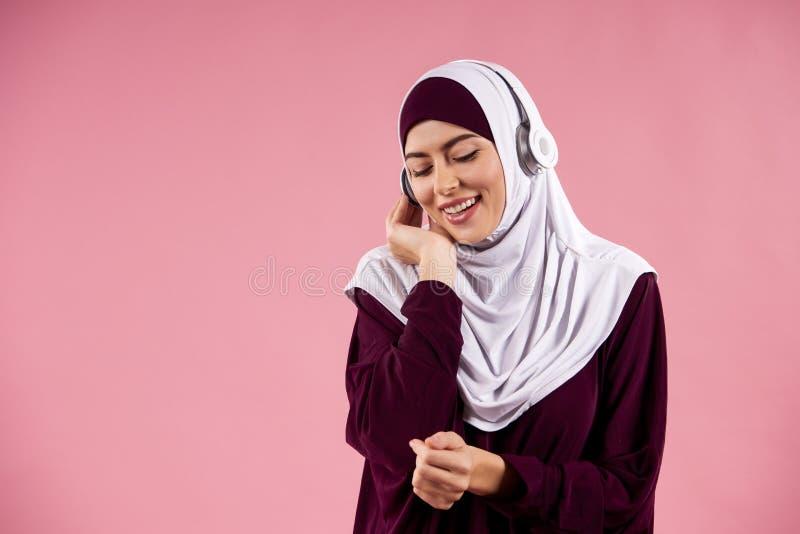 La donna araba nel hijab ascolta musica sulle cuffie fotografie stock libere da diritti
