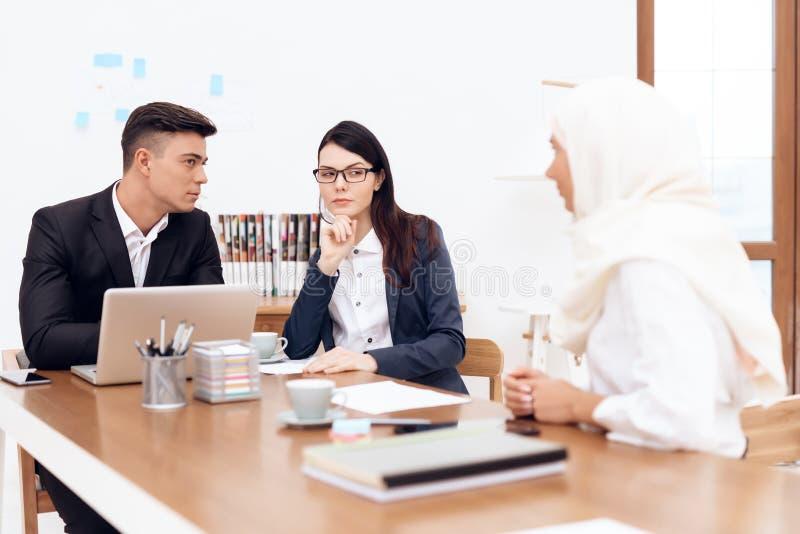 La donna araba nel hijab lavora nell'ufficio insieme ai suoi colleghi fotografia stock libera da diritti