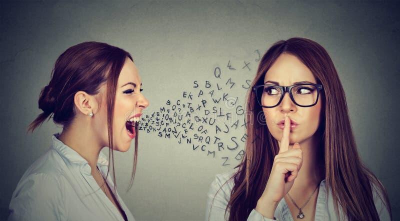 La donna arrabbiata che grida a se stessa con il dito calmo sulle labbra gesture fotografia stock libera da diritti