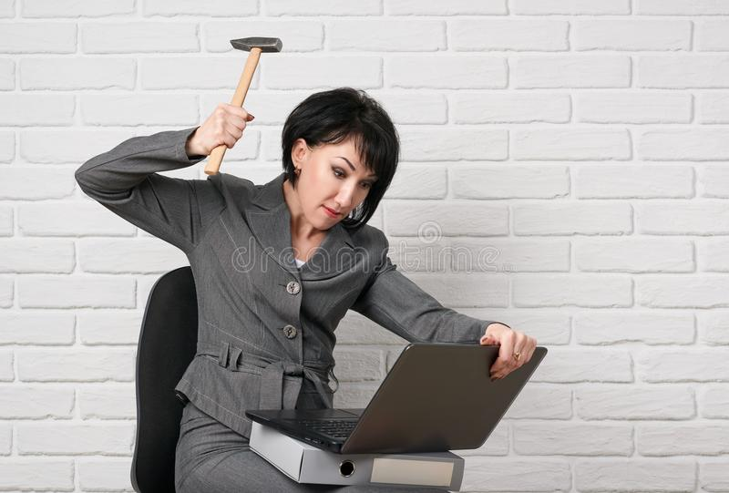 La donna arrabbiata di affari con il computer portatile e le cartelle che fanno vestirsi lo sforzo, in un vestito grigio posa dav fotografia stock libera da diritti