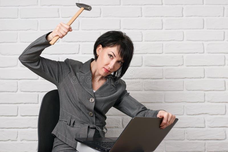 La donna arrabbiata di affari con il computer portatile e le cartelle che fanno vestirsi lo sforzo, in un vestito grigio posa dav immagine stock