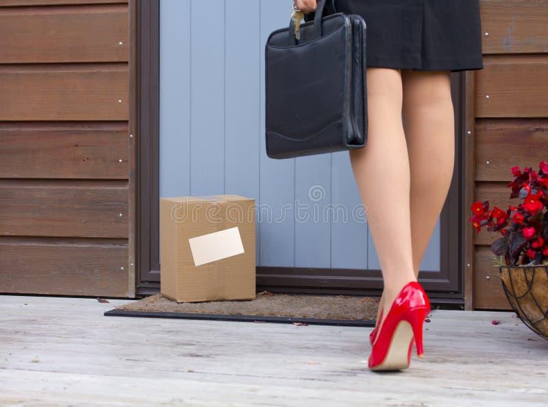 La donna arriva a casa dopo lavoro al pacchetto di consegna gratuita alla porta immagini stock