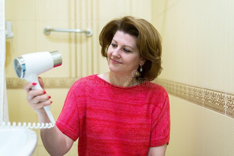 La donna asciuga i capelli fotografia stock. Immagine di ...