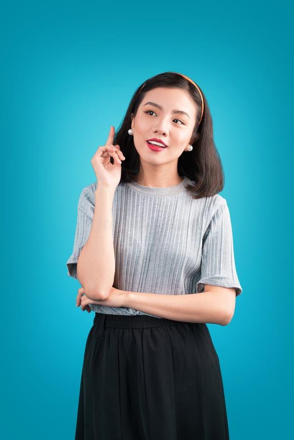La donna asiatica adorabile sorridente si è vestita in vestito da stile di pin-up sopra il bl fotografia stock