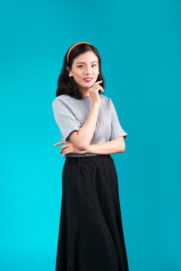 La donna asiatica adorabile sorridente si è vestita in vestito da stile di pin-up sopra il bl fotografia stock libera da diritti