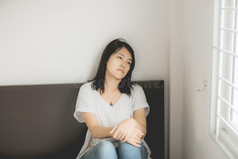 La donna asiatica che guardano qualcosa sulla finestra e la depressione hanno un'emicrania e una tristezza ritenente in camera da immagini stock libere da diritti