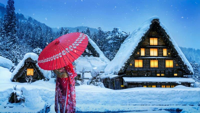La donna asiatica che porta il kimono tradizionale giapponese a Shirakawa-va villaggio nell'inverno, i siti del patrimonio mondia fotografie stock