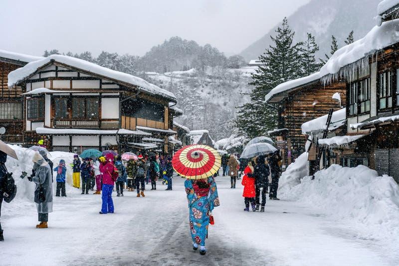 La donna asiatica che porta il kimono tradizionale giapponese a Shirakawa-va villaggio nell'inverno, i siti del patrimonio mondia immagine stock