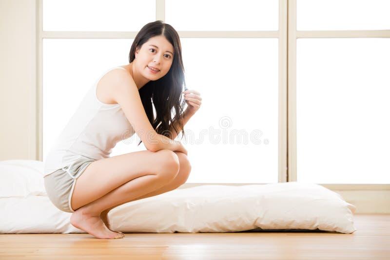 La donna asiatica che sembra radiante sveglia alla luce di primo mattino fotografia stock