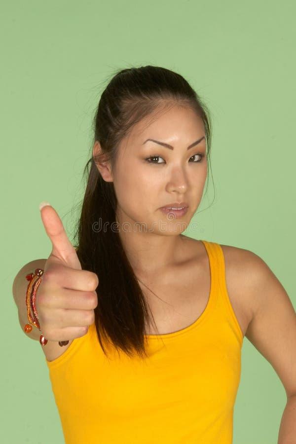 La donna asiatica con i pollici aumenta il segno fotografie stock libere da diritti