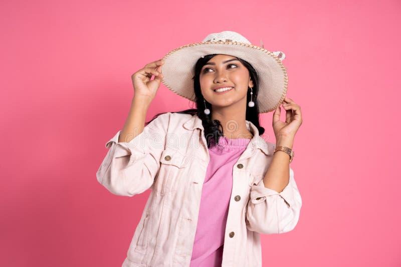 La donna asiatica con il cappello dell'estate gode di di ballare contro il rosa fotografie stock