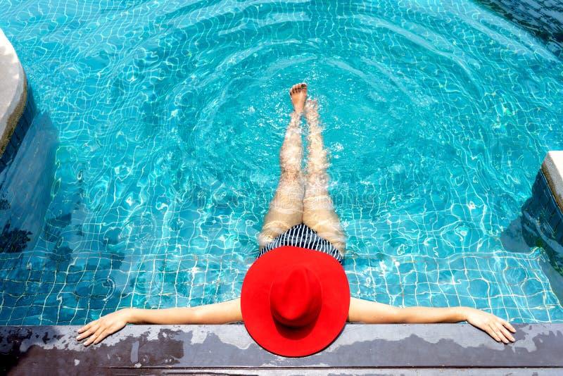 La donna asiatica con il cappello rosso si rilassa sulla piscina fotografia stock libera da diritti
