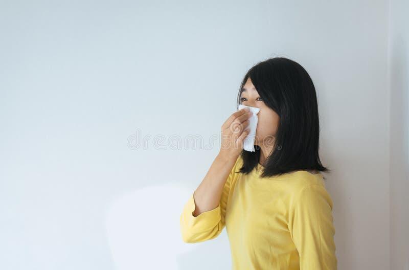 La donna asiatica con il problema di sintomi di allergia, femminile ha ottenuto il naso starnutente immagine stock libera da diritti