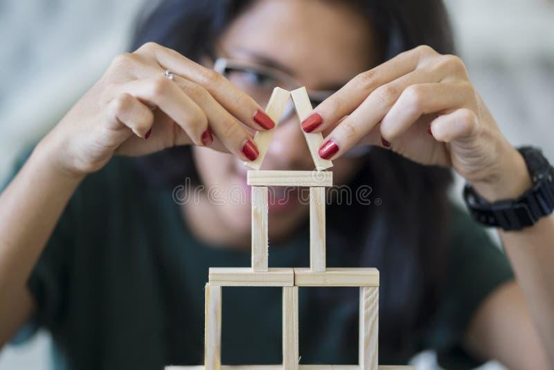 La donna asiatica costruisce una casa dei blocchi di legno immagine stock