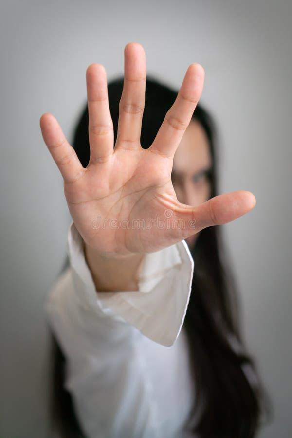 La donna asiatica dei capelli neri lunghi aumenta la sua mano fino a fermare qualcosa fotografia stock libera da diritti