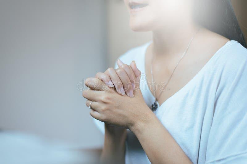 La donna asiatica felice con la mano nel pregare la posizione, mani femminili di preghiera ha afferrato insieme immagini stock libere da diritti