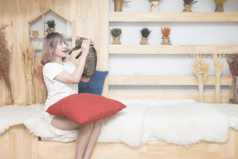 La donna asiatica felice si siede su resto del gatto della tenuta della mano del sofà a casa in collage dell'università dello gio fotografie stock libere da diritti