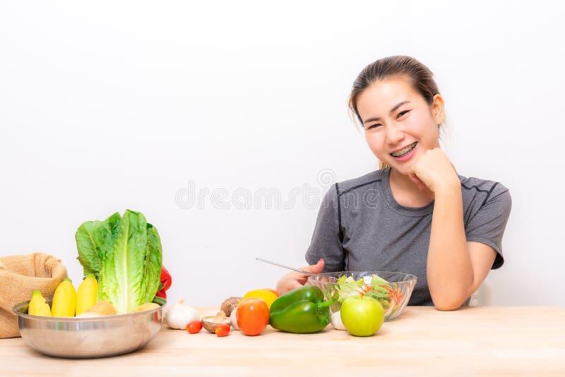 La donna asiatica gode di di mangiare la verdura di insalata fotografia stock libera da diritti