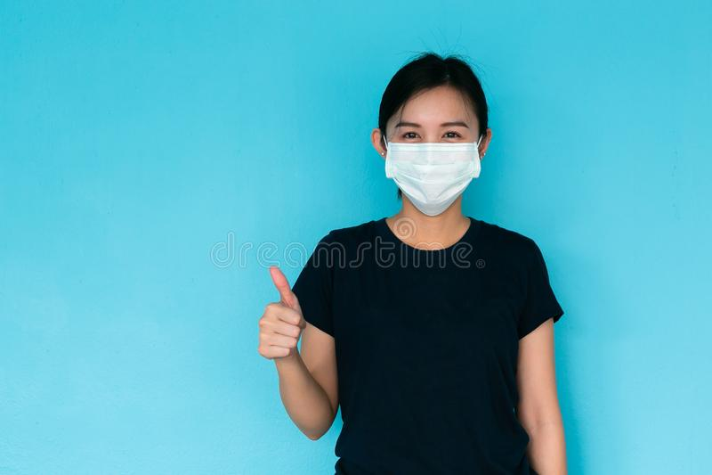 La donna asiatica indossa una maschera e un pollice su, malattia su backgroun blu fotografia stock