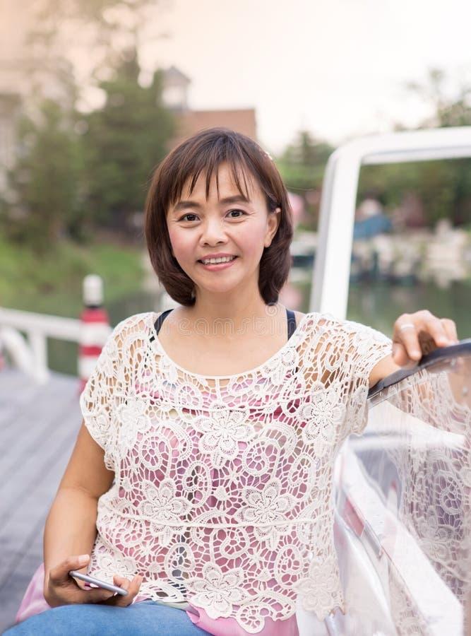 La donna asiatica matura attraente si rilassa fotografie stock