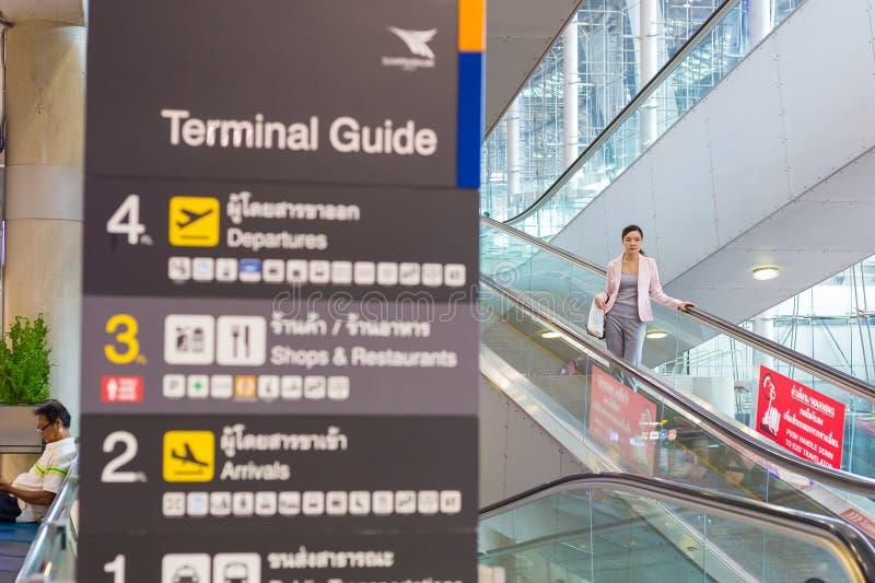 La donna asiatica non identificata scende la scala mobile dell'aeroporto a Suvarna fotografia stock libera da diritti