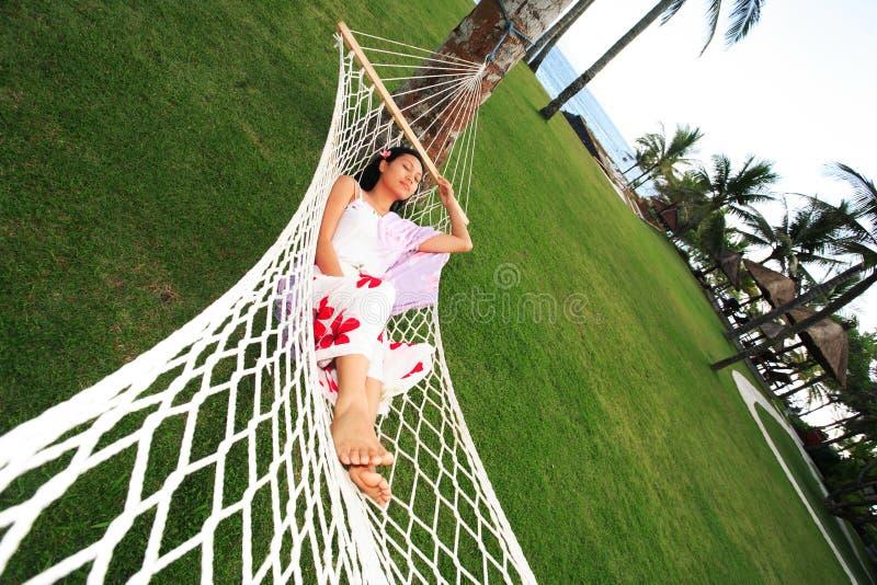 La donna asiatica si distende alla spiaggia fotografia stock libera da diritti