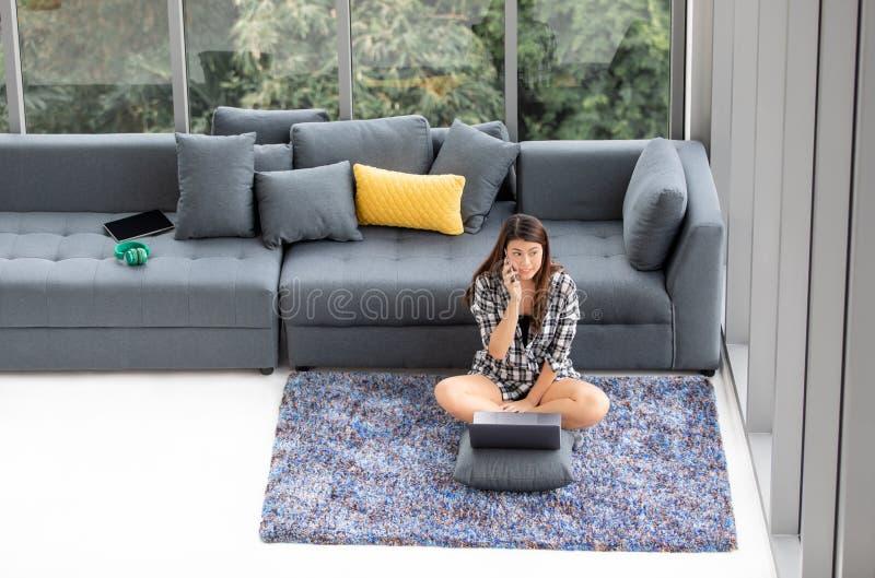La donna asiatica si siede sul tappeto del pavimento con il taccuino e sulla chiamata vicino alla s immagini stock