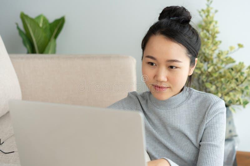 La donna asiatica sta lavorando ad un computer portatile in salone Si siede sul pavimento ed il sofà è scrivania Sul suo fronte è fotografia stock