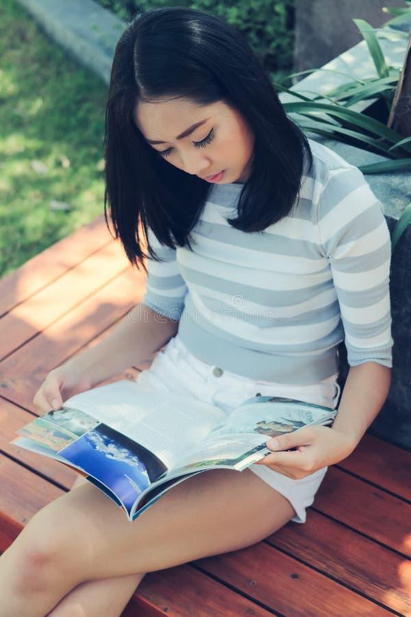 La donna asiatica sta leggendo immagini stock libere da diritti