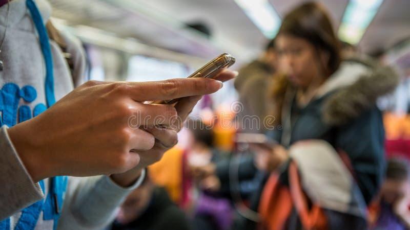 La donna asiatica sta su nel treno Facendo uso dello smartphone in sottopassaggio immagine stock