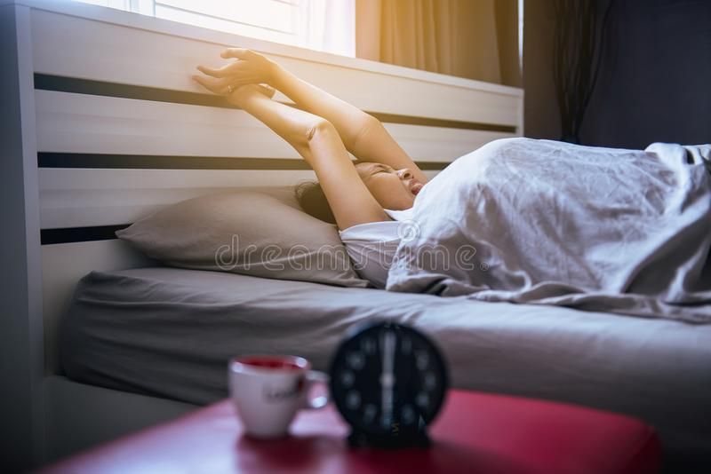 La donna asiatica sveglia l'allungamento e sbadiglia sulla sua camera da letto con la sveglia del nero della sfuocatura fotografie stock
