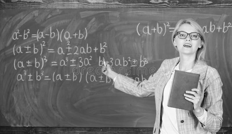 La donna astuta dell'insegnante con il libro spiega l'argomento vicino alla lavagna Maestro di scuola spiegare bene le cose e far fotografia stock