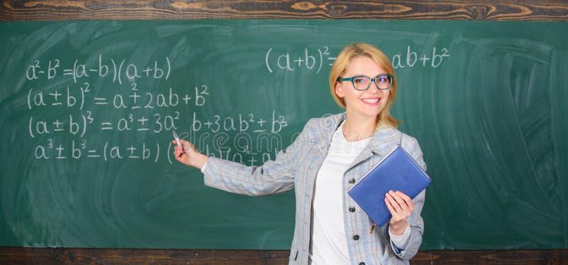La donna astuta dell'insegnante con il libro spiega l'argomento vicino alla lavagna Maestro di scuola spiegare bene le cose e far fotografia stock libera da diritti