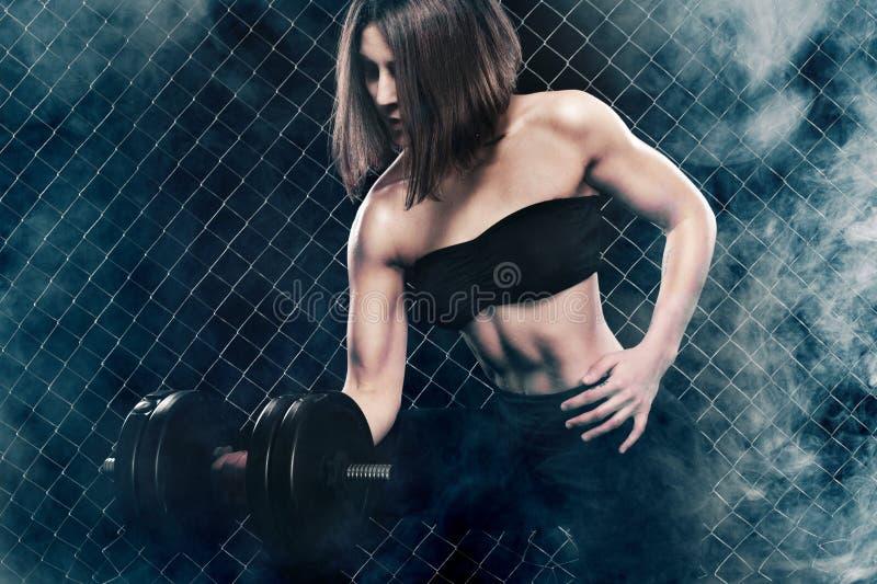 La donna atletica brutale che pompa su muscles con le teste di legno su fondo nero con fumo immagini stock