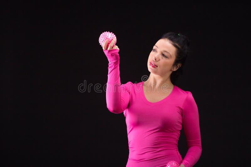 La donna atletica brutale gioca la palla sul nero fotografia stock