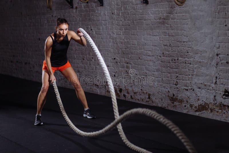 La donna atletica che fa la corda di battaglia si esercita alla palestra immagini stock libere da diritti