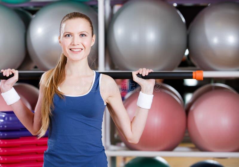 La donna atletica risolve con il bastone relativo alla ginnastica immagine stock libera da diritti