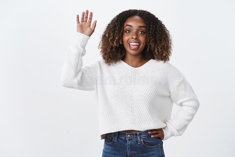 La donna attraente dell'afroamericano vivace socievole amichevole carismatico dice ciao il saluto sollevato d'ondeggiamento di ge immagine stock