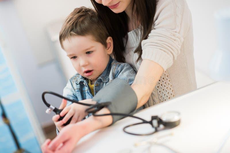 La donna attraente ed il suo bambino con una pressione sanguigna misurano il tonometer con un contatore immagini stock libere da diritti