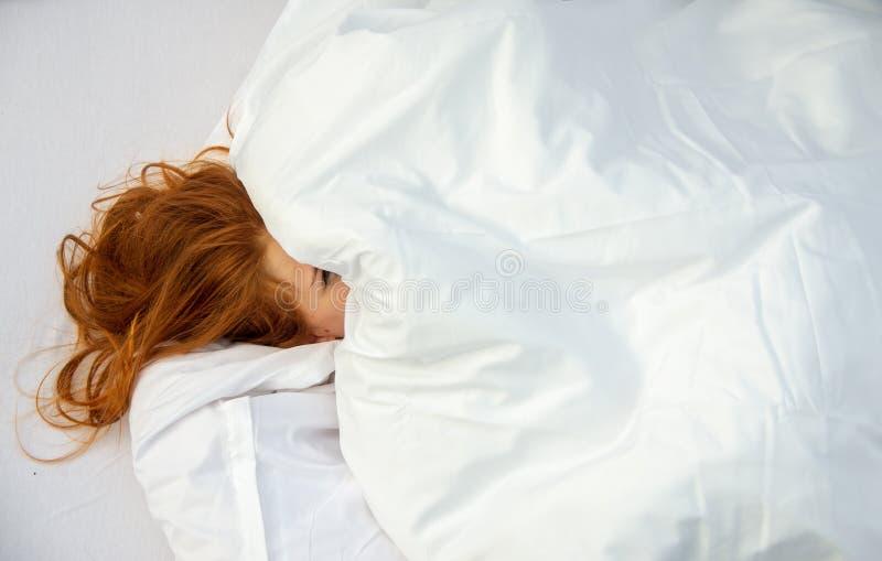 La donna attraente, giovane, sexy, dai capelli rossi, affronta quasi completamente coperto dai cuscini, un occhio sta sbirciando  immagine stock libera da diritti