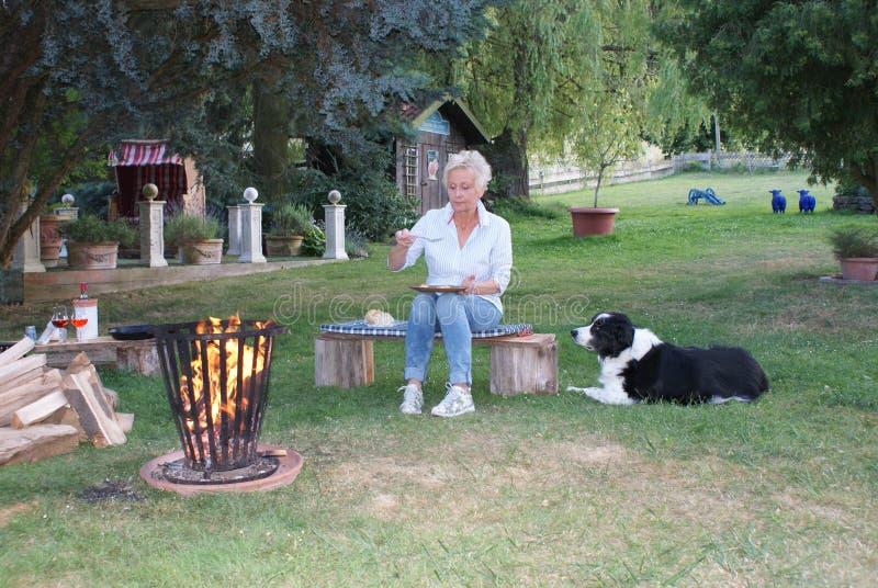 La donna attraente mangia le uova fritte al fuoco di accampamento, il suo cane sta guardando immagine stock