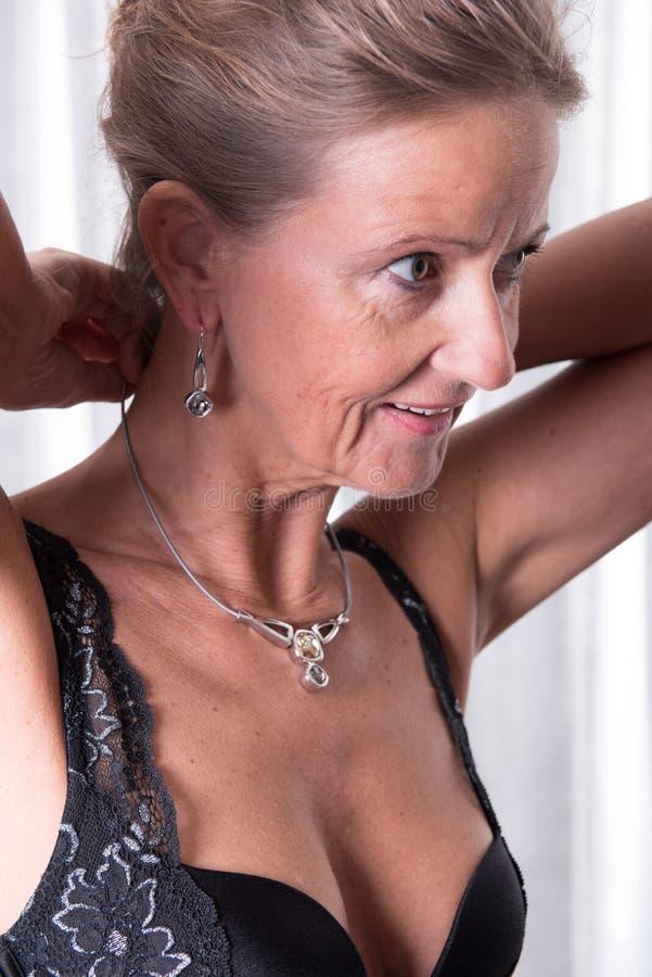 La donna attraente sta mettendo la collana sopra fotografia stock libera da diritti