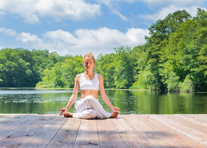 La donna attraente sta praticando la seduta di yoga nell'esercizio di Gomukasana vicino al lago La giovane donna sta meditando ne fotografia stock libera da diritti