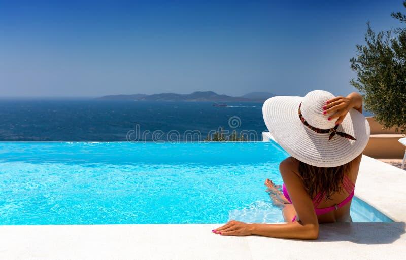 La donna attraente sta rilassandosi in uno stagno dell'infinito fotografie stock libere da diritti
