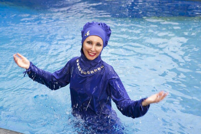 La donna attraente in un burkini musulmano dello swimwear nuota nello stagno fotografia stock libera da diritti
