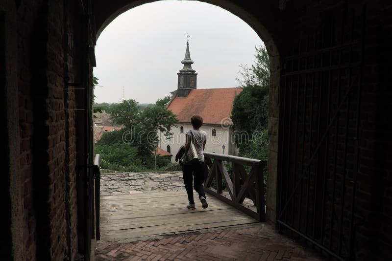 La donna attraversa il portone nella fortezza di Petrovaradin, Serbia immagine stock libera da diritti