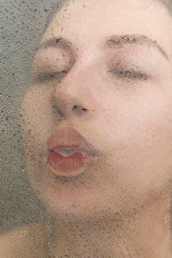 La donna bacia il vetro nella doccia immagini stock libere da diritti